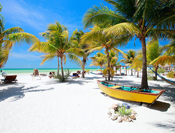 Beach beds and hammocks among palm trees at perfect tropical coast on Holbox island in Mexico