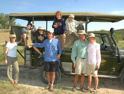 Family on safari standing in front of a 4x4 SUV