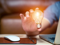 man holding lightbulb next to laptop