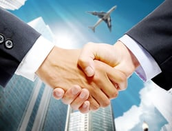 handshake with airplane in background