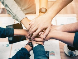 Group joining hands - collaboration (iStockPhoto)