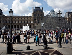 Tourists wait in line to visit the Louvre museum as it reopens.