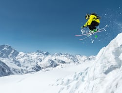 A skier in full sports equipment jumps into the precipice from the top of the glacier against the background of the blue sky and the Caucasian snow-capped mountains