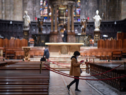 A tourist wearing a face mask walks inside the Duomo gothic cathedral as it reopened to the public after being closed due to the COVID-19 virus outbreak in northern Italy, in Milan, Monday, March 2.