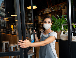 Woman wearing mask, opening door to restaurant