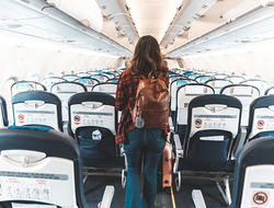 woman walking down plane aisle