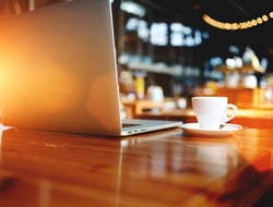 Open laptop on a wooden table in a bar or coffee shop