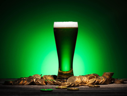 Green beer surrounded by gold coins on St. Patrick's Day