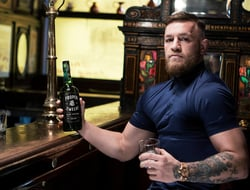 Conor McGregor with bottle of Proper No. 12 Irish whiskey at bar