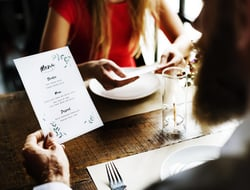 Couple at a restaurant reading the menu