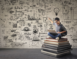 Young man with nerdy black glasses sitting on a book hill, drawing his ideas creatively on the wall behind him while looking at his computer.