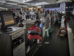 Passengers rest behind the ticket counter after the lights went out at Hartfield-Jackson Atlanta International Airport in Atlanta.
