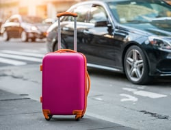 Luggage bag on the city street ready to pick by airport transfer taxi car.