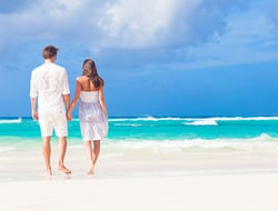 young happy couple in white at tropical beach. honeymoon