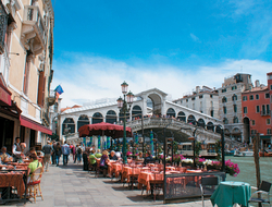Restaurant-goers in Venice have lunch outdoors with views of canal boats cruising under the Rialto Bridge.