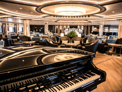 A piano in front of lounge seating at the Dolce Vita Lounge