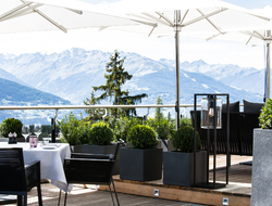 An outside eating area with the Alps in the background