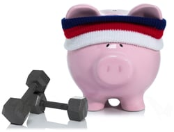 Pink piggy bank wearing sweatband with dumbbell weights