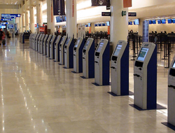 View Of Airport Self Check In Machine, People Standing, Walking, Talking To One Another Inside Cancun International Airport In Quintana Roo Mexico