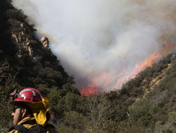 A firefighter monitors a wildfire burning along a hillside in Malibu, CA.