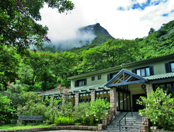 The front of Belmond Sanctuary Lodge with a cloudy mountain in the background