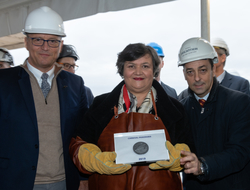 Officials from Carnival stand together with the coin in the middle