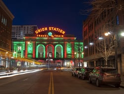 View of Union Station in downtown Denver, Colorado, taken at night from the middle of a street. The train station is lit up for the Christmas Holiday season