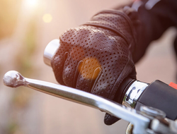 a gloved handing holding the handle of a motorcycle