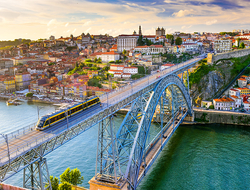 train crosses the Dom Luis I Bridge over the Douro River in Porto, Portugal
