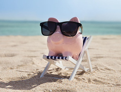 Piggy bank wearing sunglasses on a beach