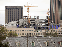 Debris hangs on the side of the building after a large portion of a Hard Rock hotel under construction suddenly collapsed in New Orleans.
