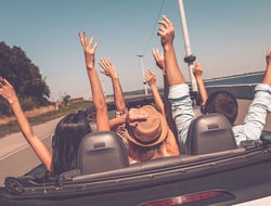 Rear view of young happy people enjoying road trip in their convertible and raising their arms up