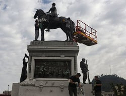 People clean the Gen. Manuel Baquedano monument in Plaza Italia, after it was vandalized amid days of demonstrations.