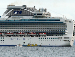 A small boat navigates near a cruise ship Diamond Princess anchoring off the Yokohama Port.