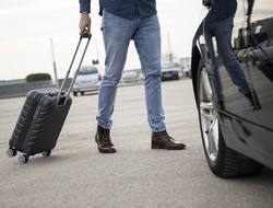 man with luggage walking to rental car