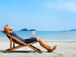 Businessman with a laptop relaxing on a beach