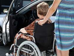 Patient in wheelchair entering car