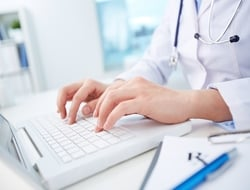 Doctor typing on laptop