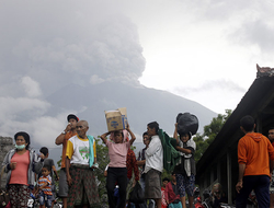 Villagers carry their belongings during an evacuation following the eruption of Mount Agung, seen in the background, in Karangasem, Indonesia.