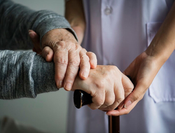 A nurse holding the hands of an elderly patient