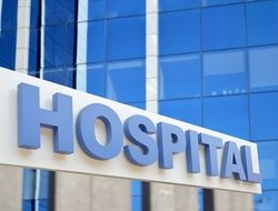 A blue hospital sign on the side of a building