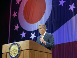 John Kasich speaking at lectern