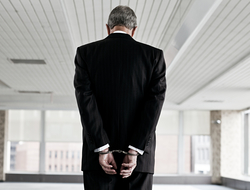 Businessman in handcuffs with his back turned