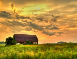 A sunset over a barn structure