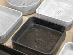 The contoured sinks are carved from solid blocks of antique gray limestone or honed Carrara marble.