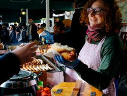 Trader at a market stall selling hot dogs at Borough Market,London, UK