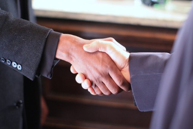 A black man and a white man shaking hands
