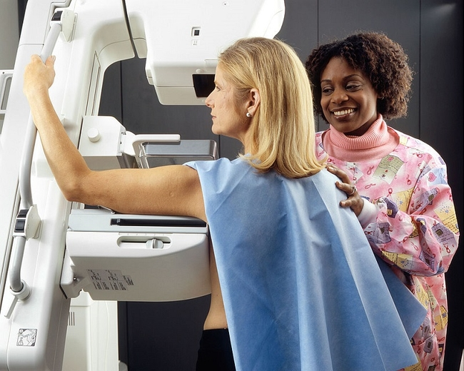 An African-American female technician positions a Caucasian woman at an imaging machine to receive a mammogram.
