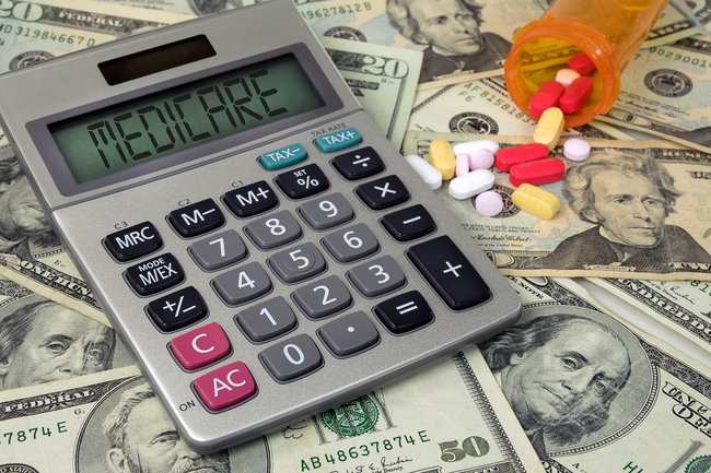 "Calculator that says ""Medicare"" on it on top of money, next to bottle of pills"