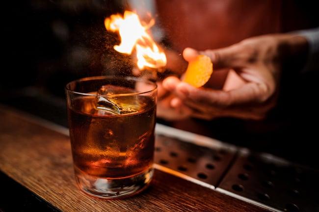 Bartender flaming an orange peel over a cocktail